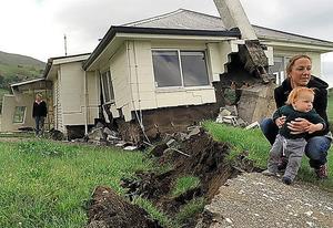 ニュージーランド南島北東部のカイコウラ近くで14日、地震で壊れた家の前にたたずむ女性と子供=AFP時事