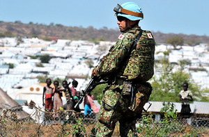<小銃手に警戒> 陸上自衛隊PKO派遣部隊の一部は、ジュバ市内の宿営地から約6・5キロ離れた国連施設付近の国内避難民保護区(後方)の防護壁を築く作業を続けている。重機を使って作業する隊員たちの傍らで、小銃を手に辺りを警戒する隊員の姿も見られた=4日、ジュバ、仙波理撮影