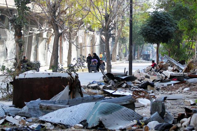 シリア北部アレッポで今月14日、戦闘で破壊された建物のがれきのそばを歩く人たち=ロイター