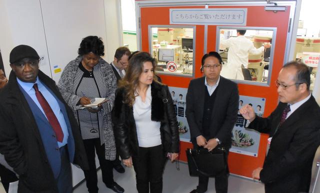食品などの放射性物質検査をする部屋を視察し、説明を受ける各国駐日大使ら=県農業総合センター