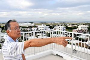 「2004年に米軍ヘリが落ちたのは、あの辺りです」と話す仲宗根清茂さん。奥に見える普天間飛行場に着陸しようとしていた=11日、沖縄県宜野湾市、小山謙太郎撮影