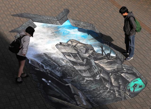 トリックアートで再現された「シリアの街」をのぞき込む人たち=17日、東京都千代田区、鬼室黎撮影