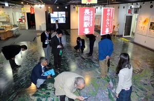 中越地震のメモリアル施設を視察する福島県3町の職員ら。フロアに印刷された地図の各被災箇所にタブレット端末をかざすと被災状況などが現れる=長岡震災アーカイブセンターきおくみらい