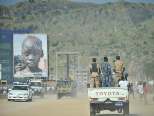 南スーダン・ジュバ市内の未舗装道路をトラックなどに分乗して走る民兵組織のメンバーたち。左は国連南スーダン派遣団(UNMISS)の看板=11月4日、仙波理撮影