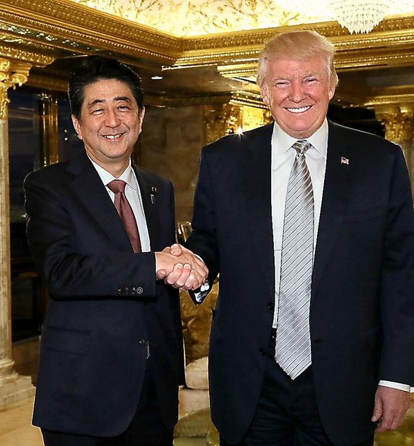 トランプ次期米大統領(右)と握手する安倍晋三首相=17日午後4時55分、米ニューヨーク、内閣広報室提供