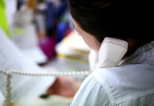 資料をめくりながら保護者と話をするワーカー。電話はひっきりなしにかかってくる