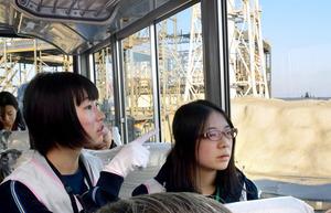 廃炉現場を見学する福島高校の生徒たち。後ろは水素爆発した1号機の原子炉建屋=18日、福島県大熊町の東京電力福島第一原発、川原千夏子撮影