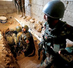 モスル近郊の町バシカで12日、IS戦闘員が使ったとみられる地下トンネルを調べるペシュメルガの隊員たち=ロイター