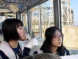 廃炉現場を見学する福島高校の生徒たち。後ろは水素爆発した1号機の原子炉建屋=18日、福島県大熊町の東京電力福島第一原発