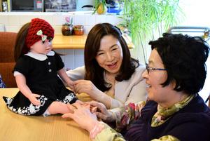 高齢者に桃色花子(左)の使い方を教える成本倖子さん(中央)=大阪府高槻市