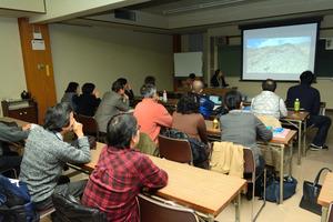 会合の冒頭、9月3日にドローンで御嶽山頂付近を撮影した動画が放映された=松本市中央4丁目、県松本勤労者福祉センター