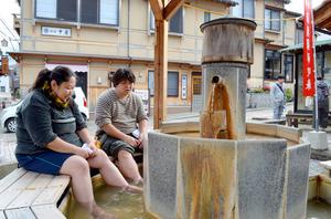 観光客の姿が戻り始めた三朝温泉街。足湯を楽しむ人の姿もあった=19日、三朝町三朝