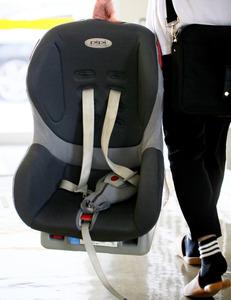 子どもを乗せるため、チャイルドシートを車に積み込むワーカー