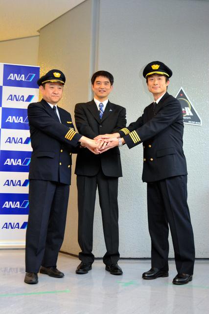 一時帰国した宇宙飛行士の大西卓哉さん(中央)。全日空パイロット時代の教官と同僚に出迎えられた=成田空港