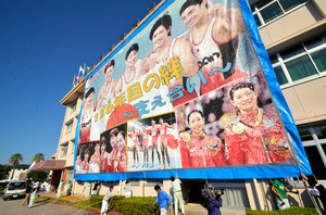 4階建ての校舎が隠れるほどのモザイク壁画がつり下げられた=南国市東崎の高知農業高校