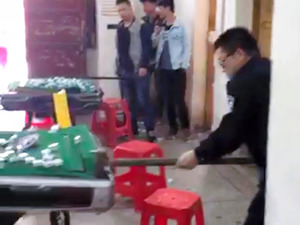 マージャン店のマージャン卓を壊す警官(中国吉林省通化、提供:関係者)
