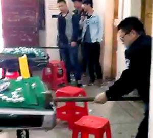 マージャン店のマージャン卓を壊す警官=中国吉林省通化、関係者提供