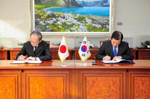 23日午前、ソウルで日韓GSOMIAに署名する長嶺安政駐韓大使(左)と韓民求・韓国国防相=韓国国防省提供