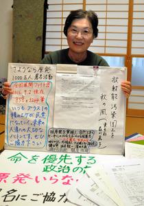 活動に使う手作りの道具を示しながら、署名1万人突破を語る角田京子さん=日立市