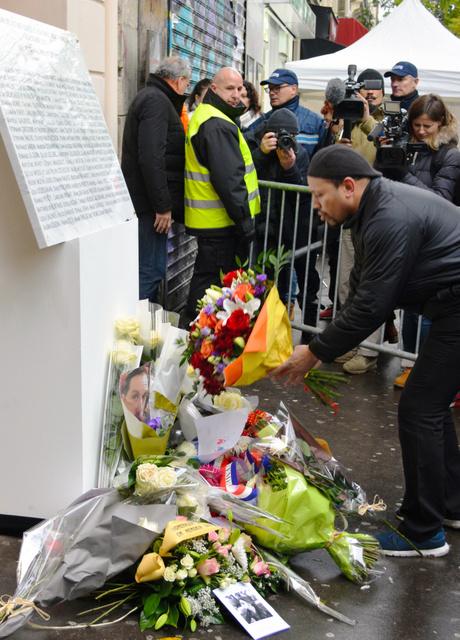 パリ同時テロから1年。90人が命を落としたコンサートホール「ルバタクラン」には犠牲者の名を刻んだプレートが設けられ、花を手向ける人が次々に訪れた=11月13日、青田秀樹撮影