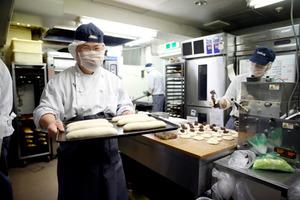 パンの生地を運ぶ加藤錦さん=東京都中央区のスワンベーカリー銀座店