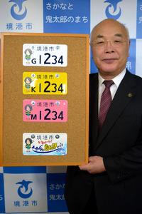 30日から導入・販売するご当地ナンバーのプレート3種とレプリカ(一番下)を持つ中村市長=境港市役所