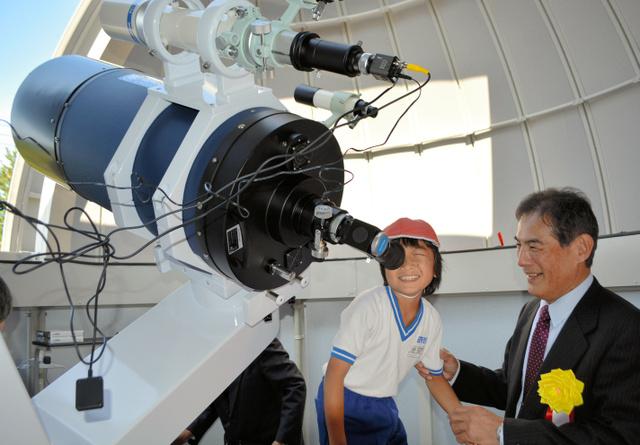完成した天文台の望遠鏡をのぞく子どもに説明する宇都文昭さん=南さつま市