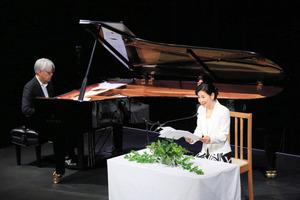カナダの朗読会で坂本龍一さんのピアノに合わせ、詩を朗読する吉永小百合さん=5月3日、カナダ・バンクーバー、内田光撮影