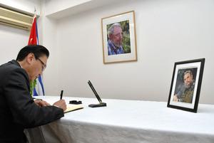 キューバのカストロ前国家評議会議長の死去に伴い、在日キューバ大使館で記帳する古屋圭司・自民党選対委員長。記帳台には生前の写真が飾られていた=東京都港区