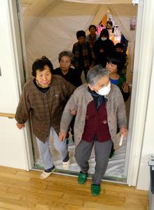 外気が侵入しないよう気圧を上げたエアテントを抜け、退避施設に入る住民ら=薩摩川内市