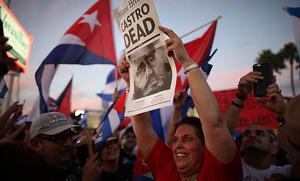 リトル・ハバナでカストロ氏死去を伝える新聞を手に喜ぶ人々=26日午後、マイアミ、矢木隆晴撮影