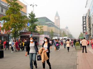 PM2.5の数値が高い日に、北京市中心部の繁華街でマスクをして歩く女性たち