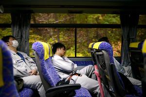 福島第一原発とJヴィレッジを結ぶ送迎バスの車内で眠る作業員たち=11月、福島県の富岡町から大熊町間、小玉重隆撮影