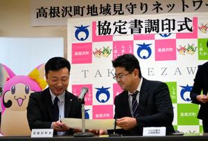 加藤公博町長(左)とASA宝積寺・山崎新聞店の高尾知道所長らが協定書にサインをした=高根沢町役場