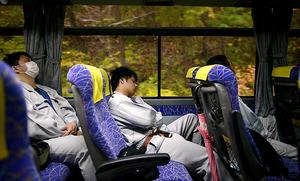 送迎バスの車内で眠る作業員たち=11月、福島県の富岡町から大熊町間、小玉重隆撮影