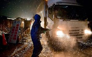 農場の入り口で、アヒルの殺処分のための資材を運んできたトラックを消毒する県の職員=29日午前0時8分、青森市四戸橋、榎本瑞希撮影