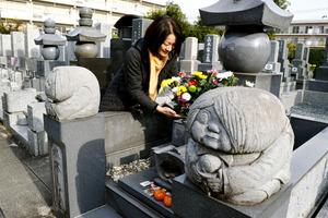 水木しげるさんの墓には多くの人が訪れ、花があふれた。花を整えているのは長女の原口尚子さん。手前は鬼太郎=調布市の覚證寺