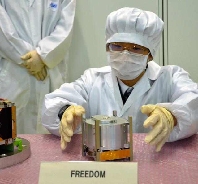 超小型衛星フリーダムを披露する中島田鉄工所の宇戸大樹さん=7日、茨城県つくば市