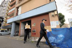 捜索を終え、押収物を持って建物を出る捜査員=1日午後0時24分、北九州市小倉北区