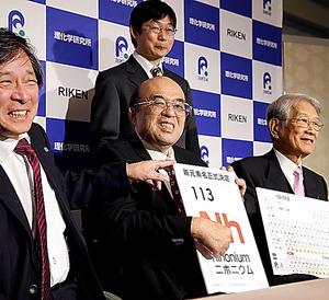 新元素記号正式決定のパネルを手に笑顔を見せる森田浩介・九州大教授(中央)=1日午前11時29分、福岡市博多区、河合真人撮影