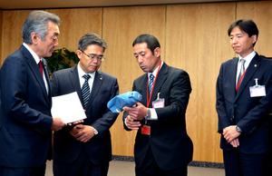 則竹崇智さん(左から3人目)がトラックにひかれて変形した水筒を見せると、松本純国家公安委員長(左端)が見入っていた=2日午前11時43分、東京都千代田区の国家公安委員会