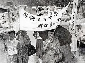 日米安保条約破棄を訴えて雨の中を歩く草の実会の「15日デモ」=1970年6月15日、東京都文京区