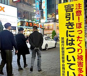 「ぼったくり」被害への注意を呼びかける看板の脇で、客引きが通行人に声をかけていた=東京都新宿区歌舞伎町1丁目