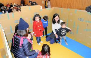 避難所に作られた段ボールによるプライベート空間に入る親子=山科区