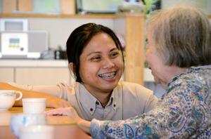 午後のおやつの時間、入居者の女性に笑顔で話しかける介護福祉士のマリシェル・オルカさん(左)=10月21日、大阪府池田市