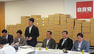 ある県で使われる段ボール118種類を背に会議に臨む小泉氏=9月、自民党本部
