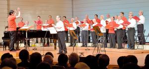 70周年を迎えた男声合唱団「コーロ・カステロ」。結成時に生まれていたメンバーは白いシャツ、その後の生まれは赤いシャツで舞台に立った=3日、狛江市の狛江エコルマホール、中山由美撮影