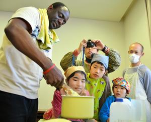 「フフ」をつくるユングさんの手さばきに見入る子どもたち=鹿児島市