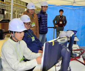 画面を見てロボットを遠隔操作する福島高専の(左から)根本晃成さん、糸井雄祐さん、小松誠司さん、佐々木和仁さん=楢葉町の日本原子力研究開発機構楢葉遠隔技術開発センター