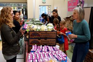保護者に無料で配るジュースや野菜を並べる学校職員やボランティアら=米国・サンフランシスコ